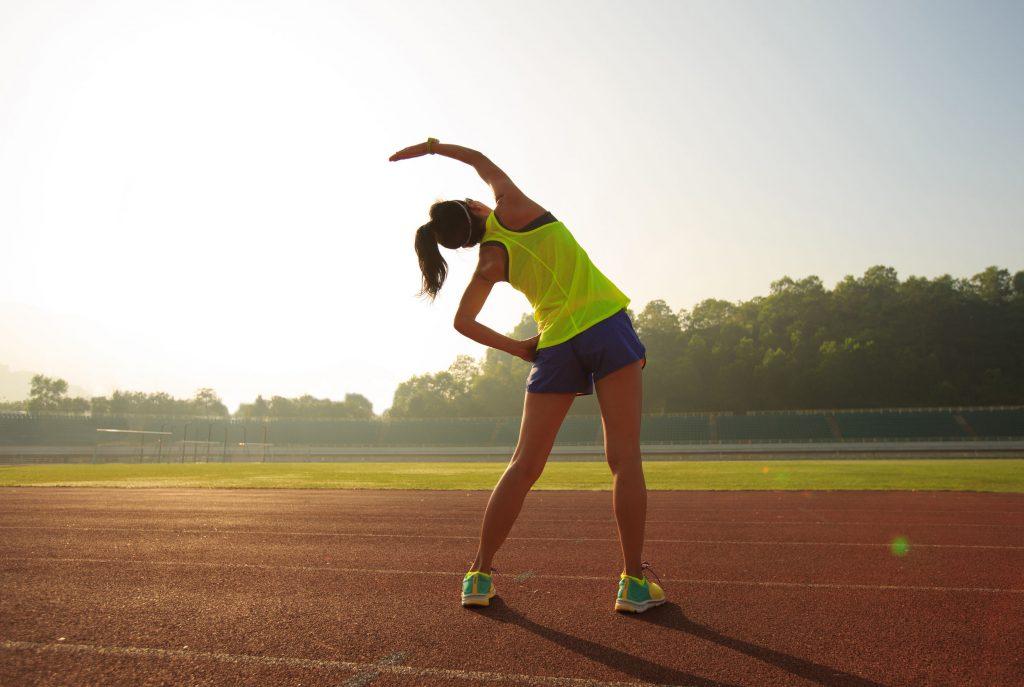 Mujer corredora ralizando calentamiento previo al ejercicio