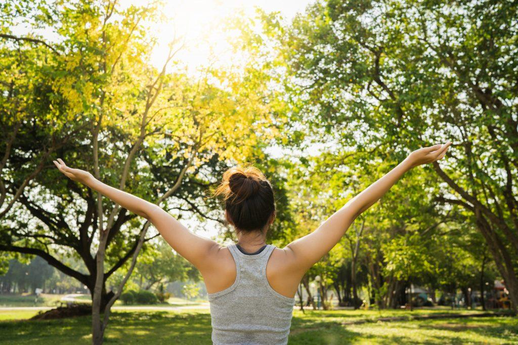 Mujer al aire libre con manos extendidas