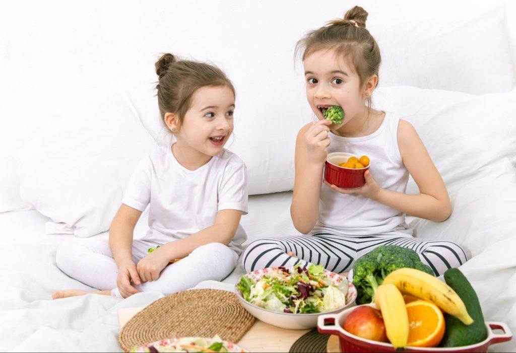 Dos niñas comiendo frutas y verduras