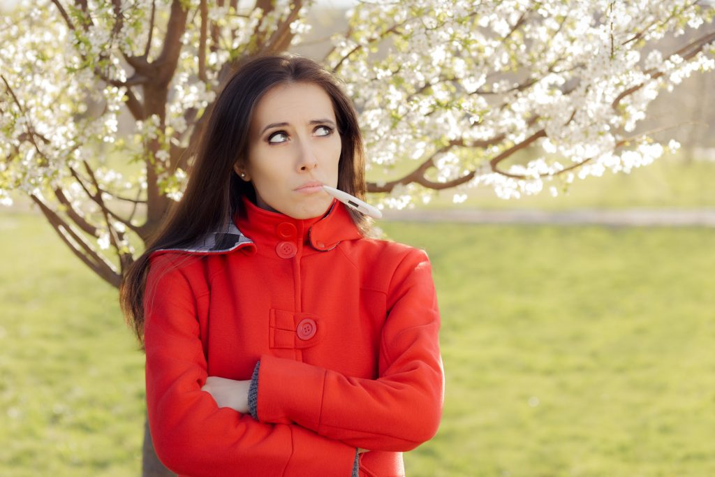 Mujer preocupada con termómetro en clima primaveral